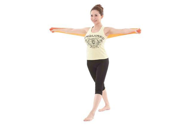 站姿,兩腳前後站,雙手向旁平舉伸直,將彈力帶放在後背。(圖片/橙實文化提供)